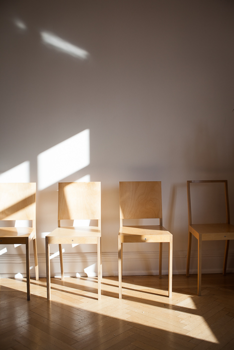 Interior of home of artist Diana Balmori, a row of chairs in sunlight lined up against wall in main room