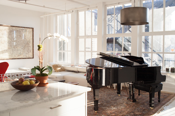 View of black grand piano from kitchen looking in to living room. Interior view of home of architect, urbanist, author, and Columbia University associate professor Vishaan Chakrabarti