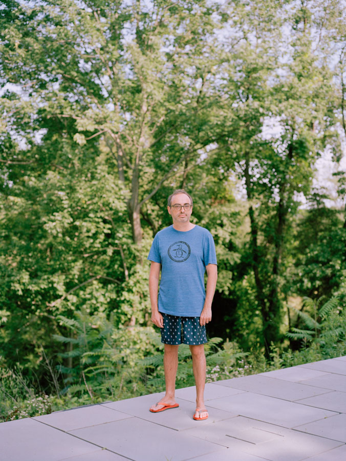 NYC Portrait photography eccentric writer Gary Shteyngart standing on pool edge with trees for German translation of book LIttle Failure Red Hook NY