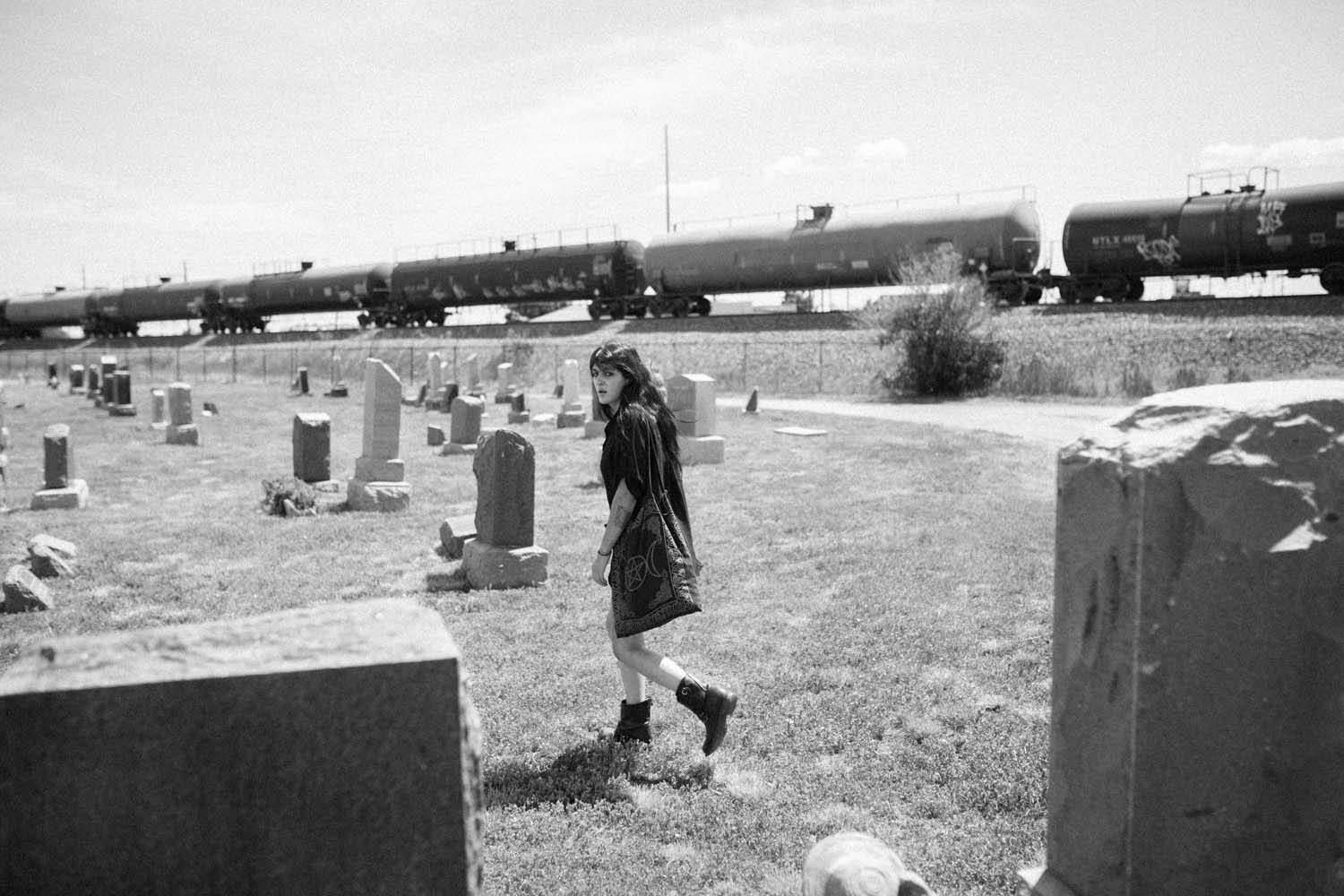 Fashion Photography NYC Street Fashion Photographer New York tattooed fashion model headstones graves Riverside Cemetery graveyard oil train passes industrial area Denver