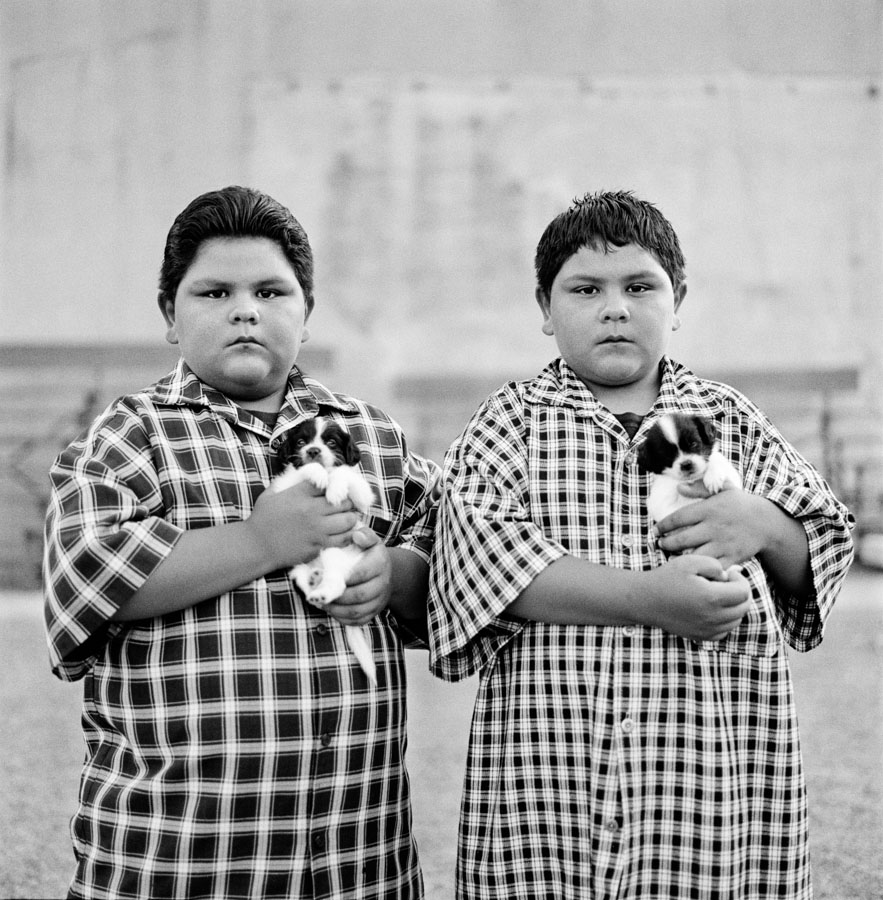 Fine art photography prints NYC | Black & white fine art print of portrait of Hispanic twin boy brothers holding puppy dogs in park. Miami, Arizona Lenscutlure