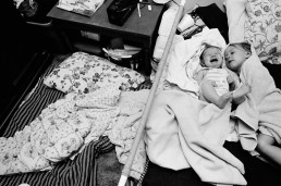 Black and White Picture of Baby Screaming on Bed as Sister Calmly Lies Wet in Towel