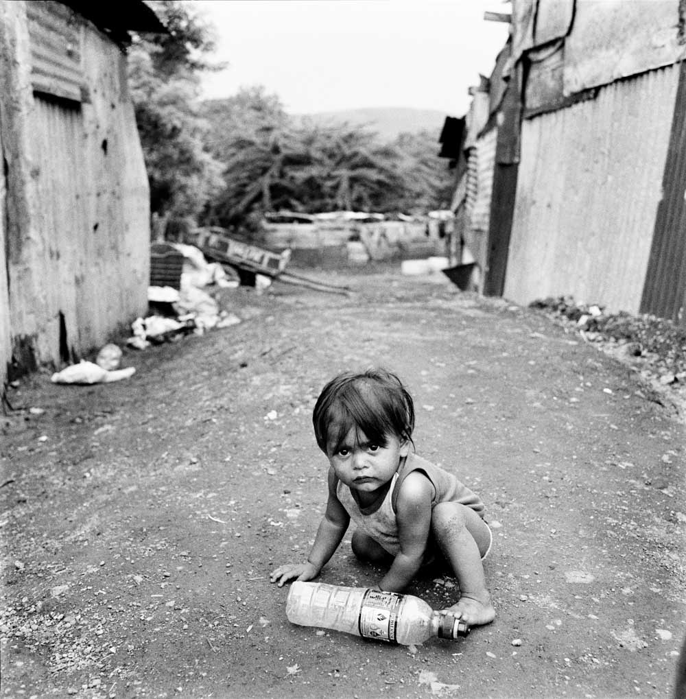 Black and White Picture of Baby in Trash Dump Sitting By Plastic Bottle Nicaragua