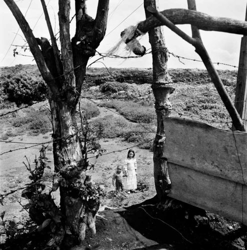 Black and White Picture of Boy & Girl in Costumes Walking by Trash Dump To School