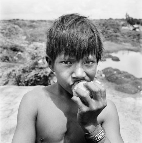 Black and White Picture of Boy Sniffing a Bottle of Glue By Trash Dump Nicaragua