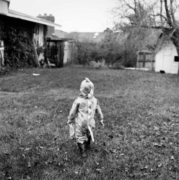 Black and White Picture of Boy in Cute Dinosaur Costume Walking Thru Grass