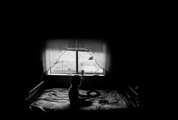 Black and White Picture of Girl Sitting Alone in Dark Room Playing a Puzzle Game Utah
