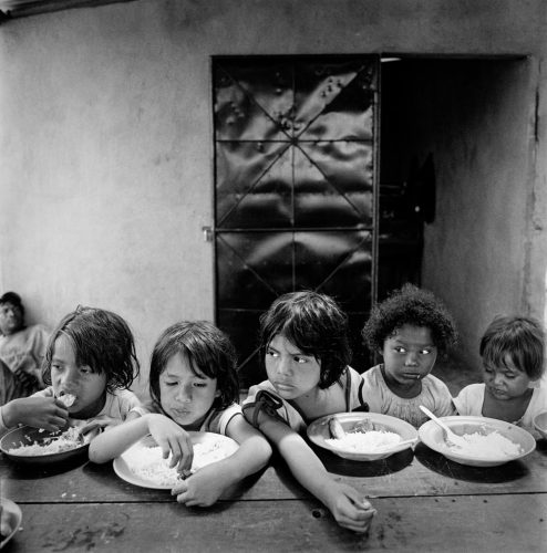 Black and White Picture of Girls Sitting at Table Eating Rice & Beans Lunch Nicaragua