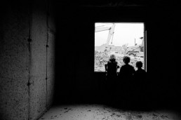 Black and White Picture of Kids Looking Out Window of Unfinished Home Construction