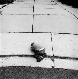 Black and White Picture of Little Boy Curled Up Pouting On Concrete Driveway Utah