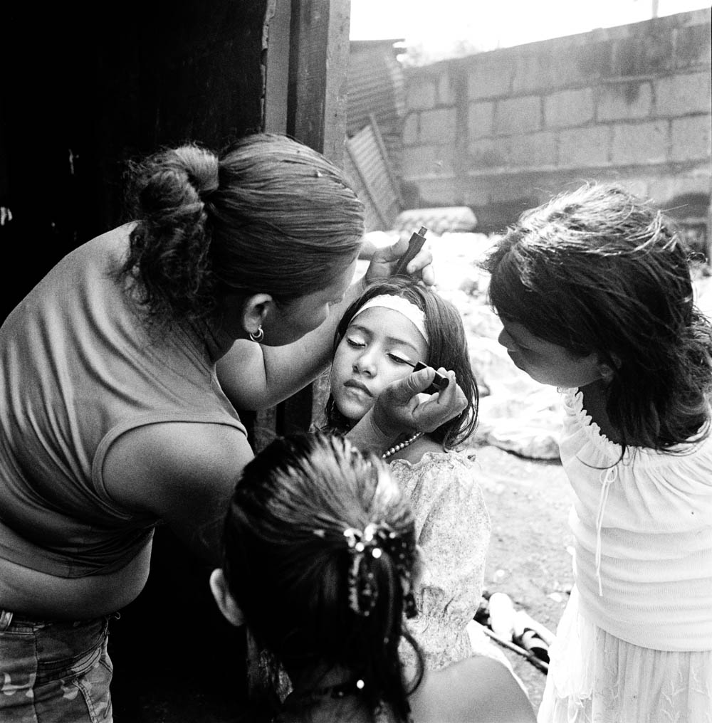 Black and White Picture of Mother Applying Make-up To Daughter As Girls Watch