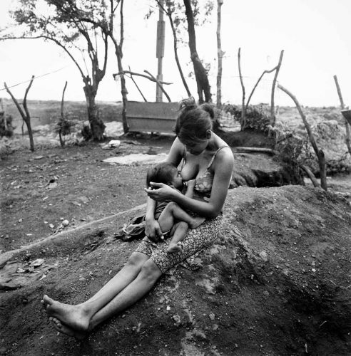 Black and White Picture of Mother Tenderly Breastfeeding Baby Son by Trash Dump La Chureca