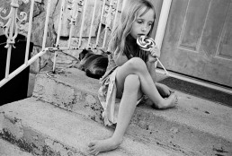 Black and White Picture of Sad Girl Licking Lollipop Candy Alone on Porch by Cat