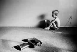 Black and White Picture of Sick Semi-Nude Boy Sitting on Floor by Heater & Boots Utah