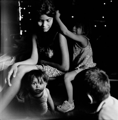 Black and White Picture of Teen Mother Playing with Children inside Tin Home