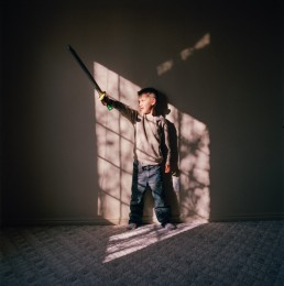 Dramatic Picture of Boy Holding up Toy Sword in Bright Window Light Utah