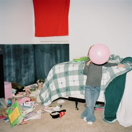 Funny Picture of Pink Balloon Covering Girl's Face Standing in Messy Bedroom Denver