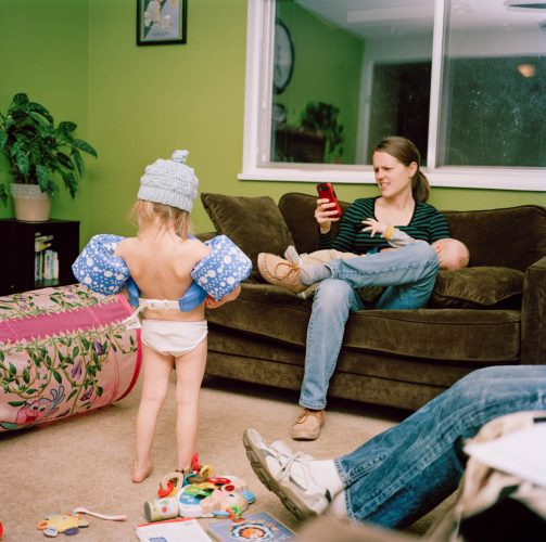 Funny Picture of Small Girl in Underwear & Floaties as Mother Breastfeeds on Phone
