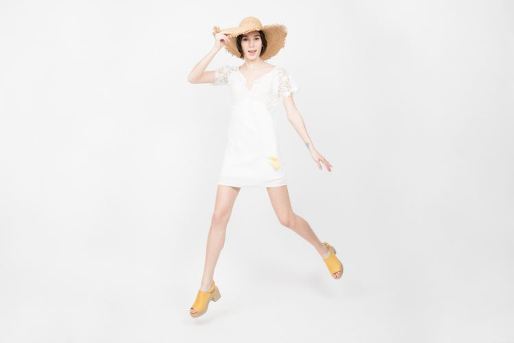 Image of Fashion Model in White Dress Jumping in Studio for French Designer