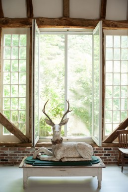 Interior Photos of Two Barns, Wooden Deer Sculpture on Table in Bridgehampton Home