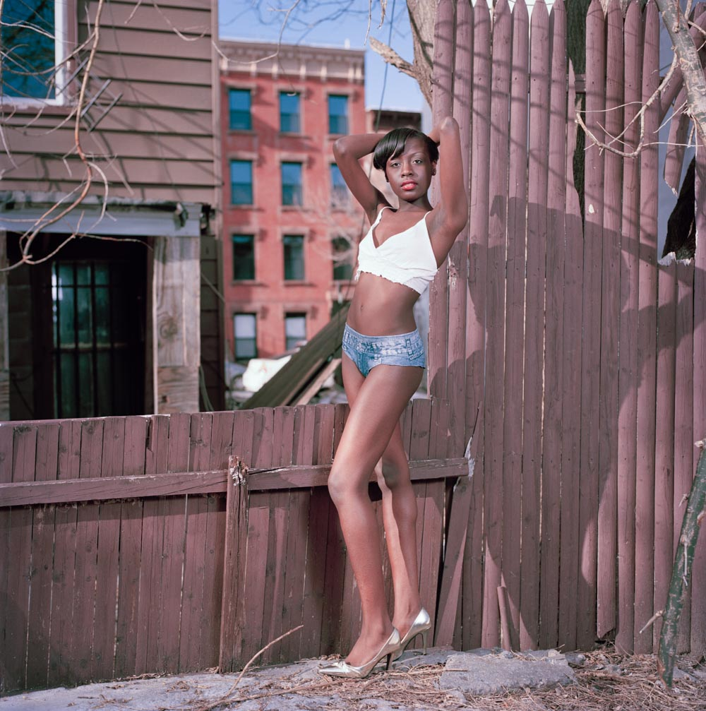Picture of Beautiful Slim Black Teen Fashion Model by Fence in Urban Lot NYC