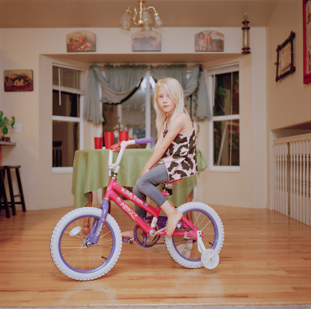 Picture of Blonde Girl Riding a New Bicycle & Birthday Gift in Family's Kitchen Utah