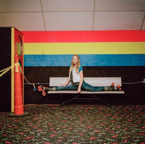 Picture of Blonde Teen Girl Doing Splits on Bench at Roller Skating Rink Utah