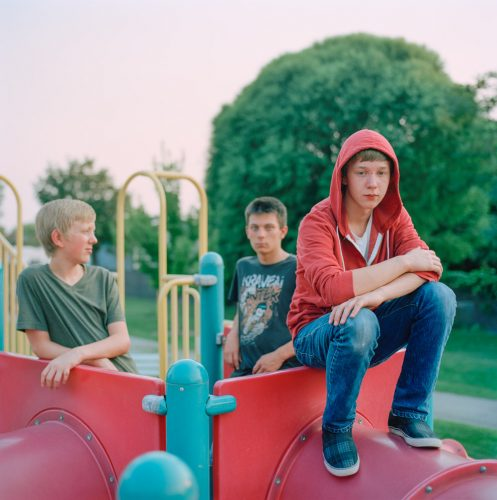 Picture of Group of Bored Teen Boys Sitting on Slide at Park Playground at Sunset Utah