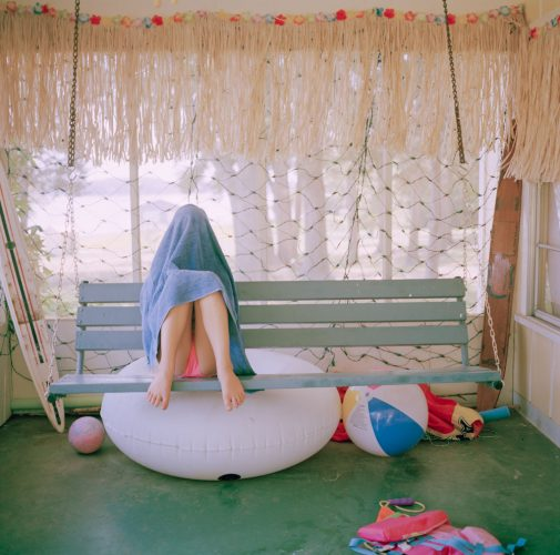 Picture of Mad Teen Girl in Swimsuit Head Covered by Towel on Swing At Lakehouse