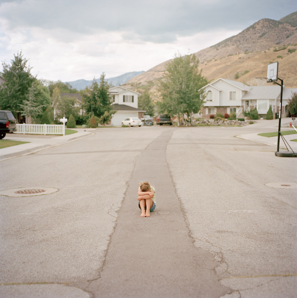 Picture of Small Girl Pouting Crouched in Middle of Street by Mountains Utah