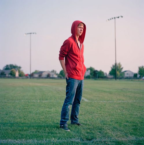 Picture of Teen Boy in Red Hoodie Standing Alone in Park Baseball Field Utah