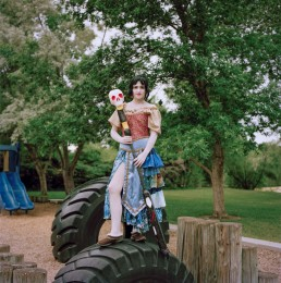 Picture of Woman In Medieval Costume & Skull Staff Standing on Tractor Tire in Park