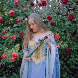 Picture of Woman In Medieval Princess Costume Holding a Dagger by Rose Bushes
