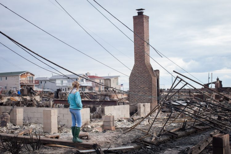 Picture of girl by homes destroyed by fire in Breezy Point Queens after Hurricane Sandy
