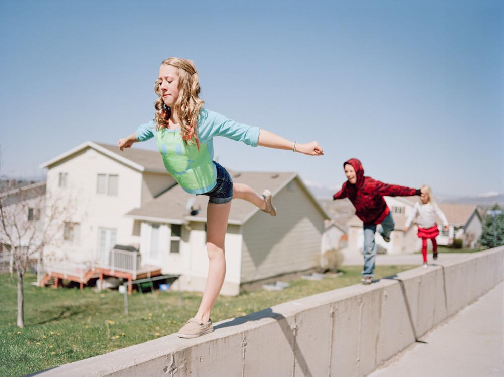 Photo of blonde teenage girl doing gymnastics on concrete ledge as siblings copy Utah