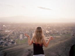 Photo of blonde teen girl on hill looking out over valley from mountains at sunset Utah