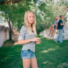 Picture of angry blonde teenage girl in suburban yard by friends summer Utah