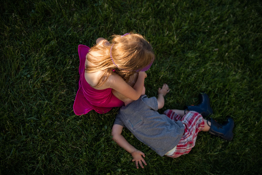 Picture of girl in pink mermaid costume playing and hugging brother on grass Denver