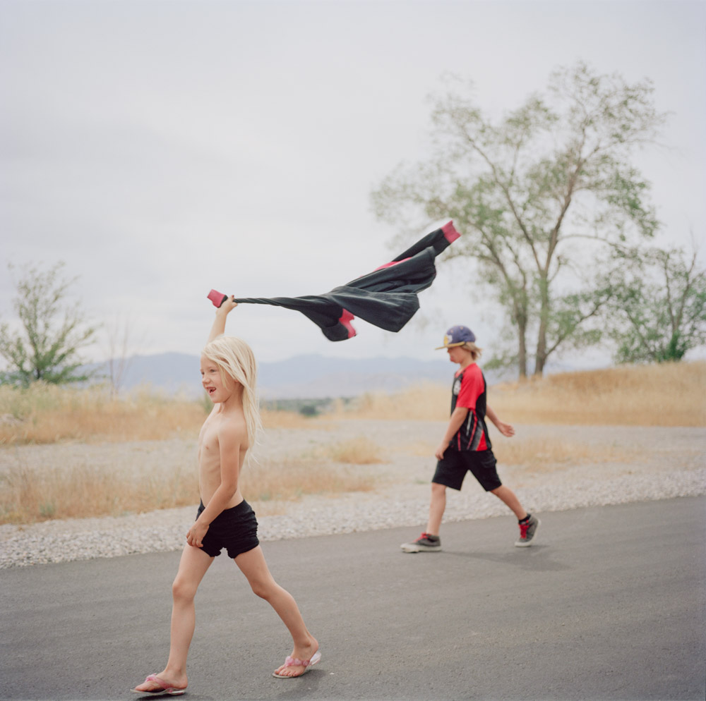 Picture of shirtless blonde girl on path twirling sweater on summer day by brother