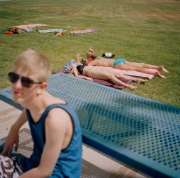 Picture of teenage boy in sunglasses sitting at bench near sunbathing teen girls summer