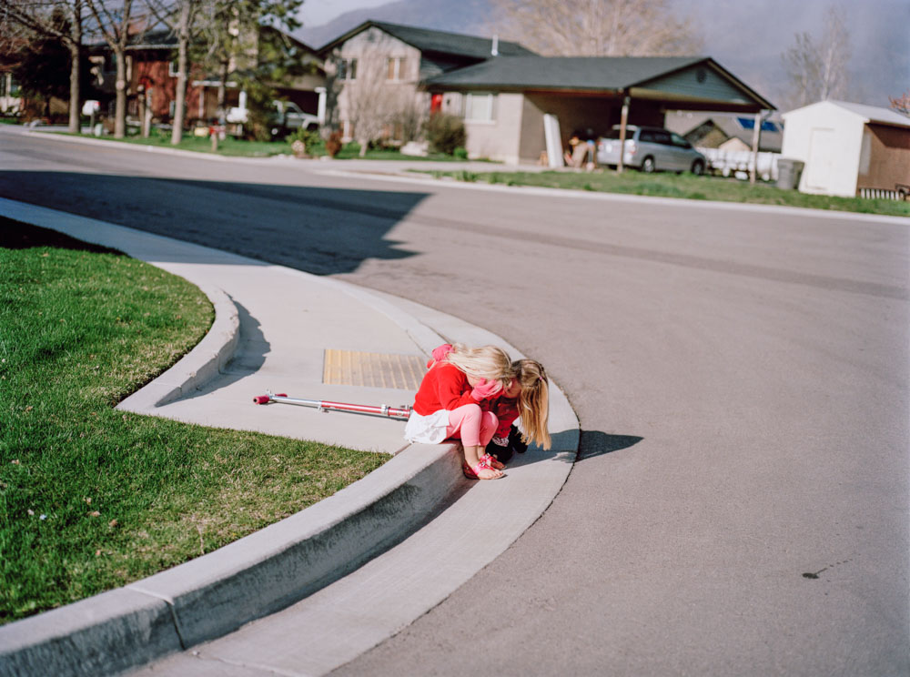 Picture of young girl crying on street corner as cousin lovingly comforts her Utah