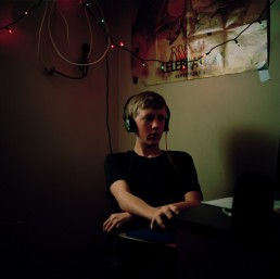 Portrait of teen boy computer geek in dark room listening to headphones on computer