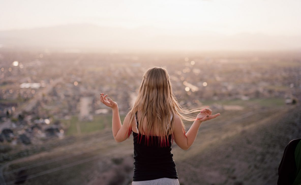 Photo blonde teen girl on hill looking out over valley from mountains at sunset Utah