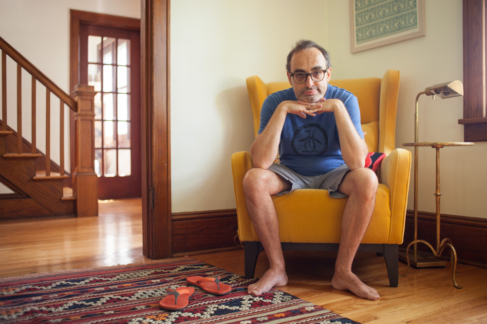 Photo of Writer Gary Shteyngart Sitting on Yellow Chair at Red Hook Home