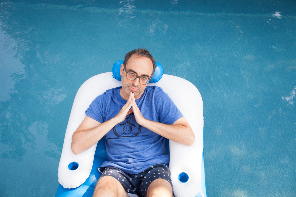 Photo of writer Gary Shteyngart lying floaty pool water German translation book LIttle Failure Red Hook NY