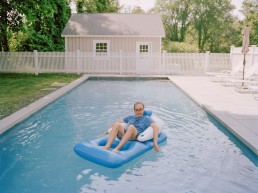 Photo of writer Gary Shteyngart lying on floaty in pool water for German translation of book LIttle Failure Red Hook NY