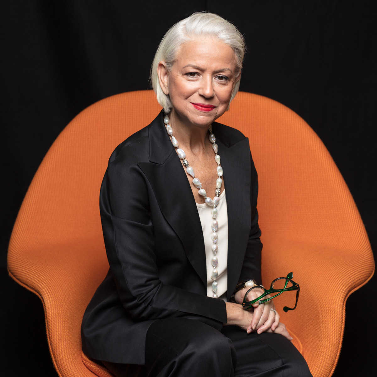 Modern, editorial portraits for NYC law firm elderly lawyer in stylish orange chair