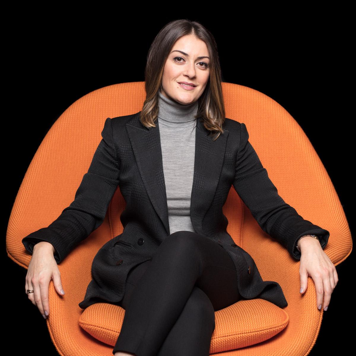 Modern, editorial portraits for NYC lawyers pretty lawyer in stylish orange chair