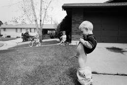 Fine Art Black and White Picture of Boy Peeing on Lawn as Girls Watch