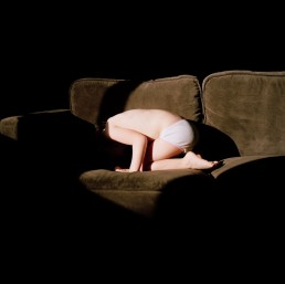 Haunting Fine Art Picture of Little Girl Playing in Underwear on Couch at Child's Home